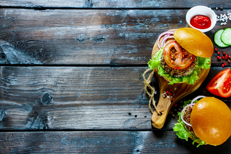 Foto de Fresh veggie burgers with quinoa patty, lettuce and tomato sauce, served on little wooden board over dark wooden background, top view. Clean eating, detox, vegetarian food concept - Imagen libre de derechos