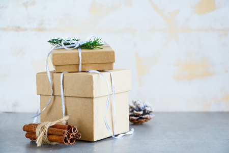 Photo pour Holiday gift or present box wrapped in kraft paper, Fir Branches and Festive Decoration on Stone Background, Christmas Greeting Card, Selective focus - image libre de droit