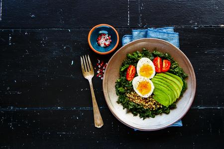 Foto de Fresh vegetarian salad bowl of quinoa, kale, tomatoes, avocado and egg over black wooden background, top view, copy space. Flat lay style. Energy boosting food concept - Imagen libre de derechos