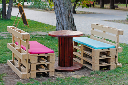Photo pour Wooden bench made of pallets for sitting with table made from coil of electric cable outdoors - image libre de droit
