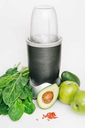 fitness blender with a set of healthy products, apple avocado spinach on a white background