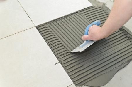 Photo pour Laying Ceramic Tiles. Troweling mortar onto a concrete floor in preparation for laying white floor tile. - image libre de droit