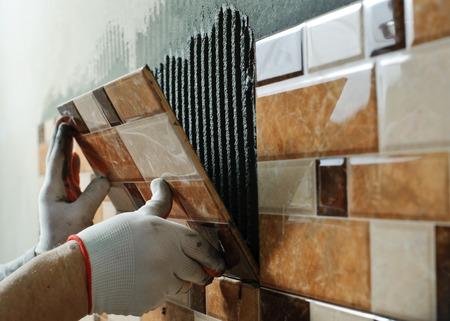 Photo pour Laying Ceramic Tiles. Tiler placing ceramic wall tile in position over adhesive - image libre de droit
