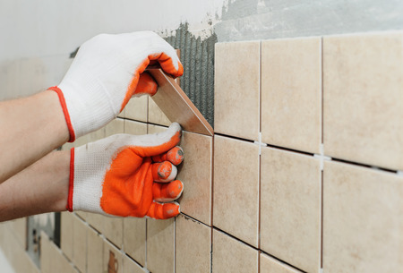 Photo pour Worker sets  tiles on the wall in the kitchen. His hands are placing the tile on the adhesive. - image libre de droit