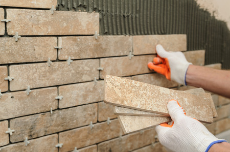 Photo for Installing the tiles on the wall. A worker putting tiles in the form of brick. - Royalty Free Image