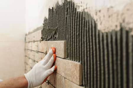 Photo pour Installing the tiles on the wall. A worker putting tiles in the form of brick. - image libre de droit