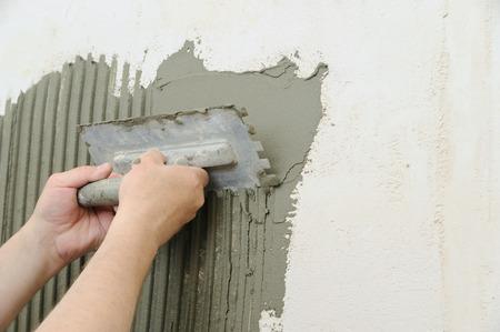Foto de Tilers hands are putting on a tile adhesive on the wall in the bathroom. - Imagen libre de derechos