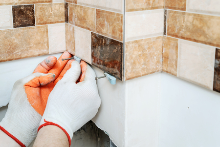 Photo for The tiler's hands are using plastic wedges to align tiles on the wall. - Royalty Free Image
