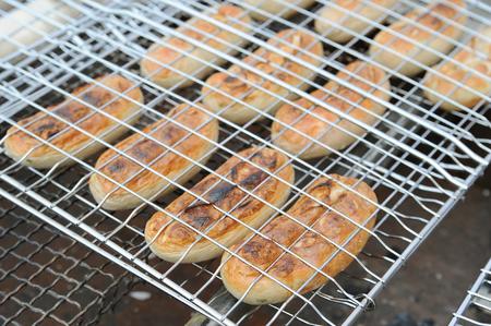 Foto de Preparation of sausages on a grill lattice - Imagen libre de derechos