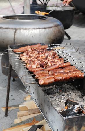Foto de Preparation of sausages and shashlik on a brazier - Imagen libre de derechos