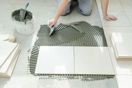 Foto de A tiler is putting tiles adhesive to the wall with the notched trowel. - Imagen libre de derechos