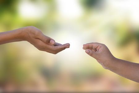Foto de two hands reaching out with blurry background behind - Imagen libre de derechos