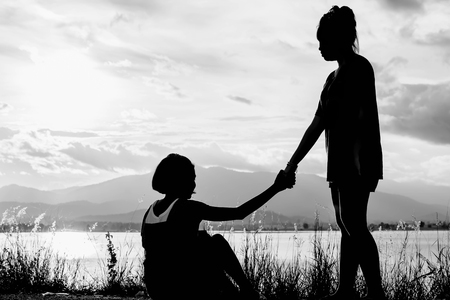 Foto de young girl help another girl to stand with lake view at sunset in white tone - Imagen libre de derechos