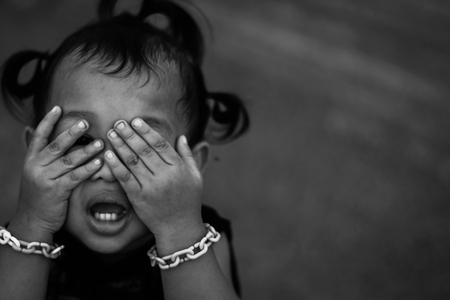 Foto de photo of children hand cover face with with crying , retarded, Child Abuse in white tone with shadow edge - Imagen libre de derechos
