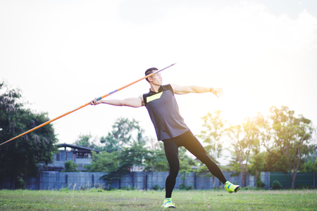 Photo for sportsman warming up and practicing javelin throw in yard - Royalty Free Image
