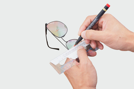 Photo pour The ophthalmologist determines the distance centers of the lenses with ruler tool. Optician measuring and preparing glasses - image libre de droit