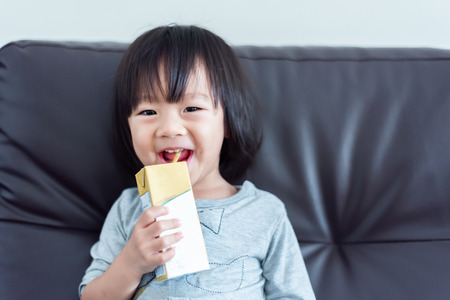 Photo pour Happy Sweet Asian baby child drinking a carton of milk from box with straw on sofa - image libre de droit