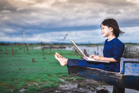 Foto de Asian children in local dress are using laptop for education and communication at countryside of Thailand. - Imagen libre de derechos