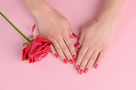 Foto de Hand with red nails. Color inspired by hue of rose flower. Getting simple and nice style at manicure salon. - Imagen libre de derechos