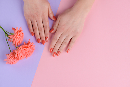Photo pour Coral pink nails and flowers. Bright color for a romantic person. Manicure salon background with copy space. - image libre de droit