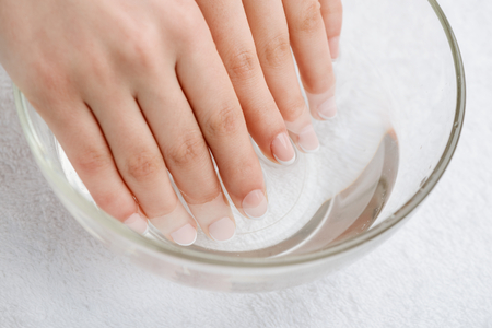 Photo pour Warm bath for nails and dry skin. Mix of water and oil to soften cuticle. Proper care for hands. - image libre de droit