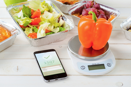 Photo pour Calorie counter app on the smartphone, a kitchen scale and a fresh pepper on the wooden surface, close-up. Lettuce and tomato salad, grapes on the background. Counting calories. - image libre de droit