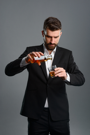 Foto de Concentrated man pouring whisky - Imagen libre de derechos