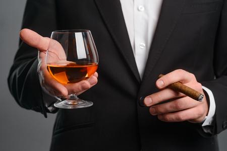 Foto de Cigar and glass in hands - Imagen libre de derechos