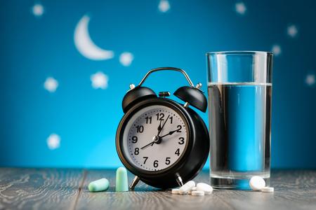 Foto de Clock, earplugs, pills and water - Imagen libre de derechos