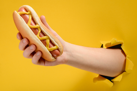 Photo for Hand taking a traditional hotdog - Royalty Free Image