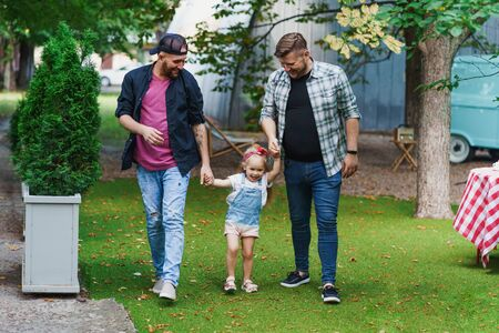 Photo for Gay couple with little daughter walking in the park - Royalty Free Image