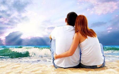 Photo pour Sea view of a couple sitting on beach. - image libre de droit