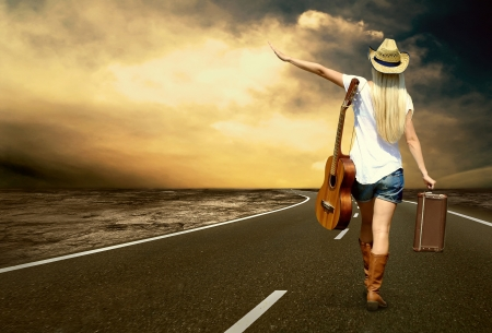 Foto de Young woman with guitar on the road and her vintage baggage - Imagen libre de derechos