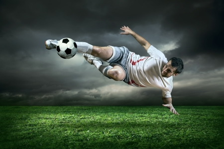 Photo pour Football player with ball in action under rain outdoors - image libre de droit