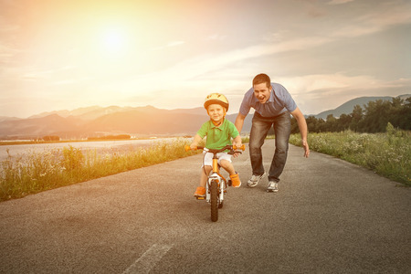 Foto de Happiness Father and son on the bicycle outdoor - Imagen libre de derechos