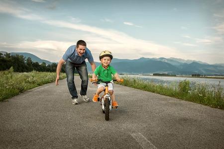 Foto de Happiness Father and son on the bicycle outdoor - Imagen libre de derechos