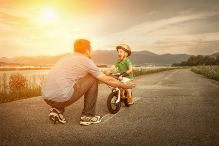 Photo for Father and son on the bicycle outdoor - Royalty Free Image