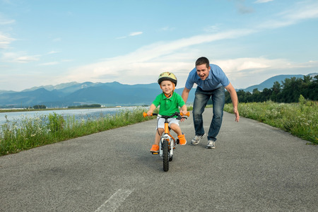Photo for Happiness Father and son on the bicycle outdoor - Royalty Free Image
