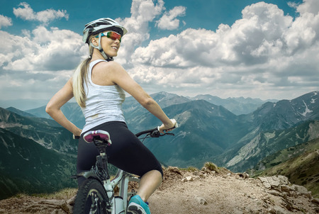 Photo for Beautiful woman in helmet and glasses stay on the bicycle around mountains. - Royalty Free Image