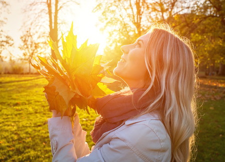 Photo pour Happiness woman with leafs in autumn under sunlight - image libre de droit