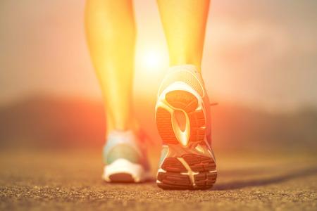 Photo pour Runner athlete feet running on road under sunlight. - image libre de droit