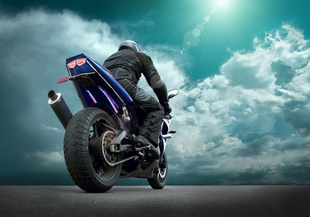 Foto de Man seat on the motorcycle under sky with clouds - Imagen libre de derechos