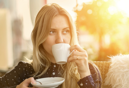 Photo for Beautiful blonde female drink coffee in cafe - Royalty Free Image