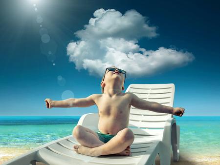 Foto de Child in sunglasses fun near the water under sunlight - Imagen libre de derechos