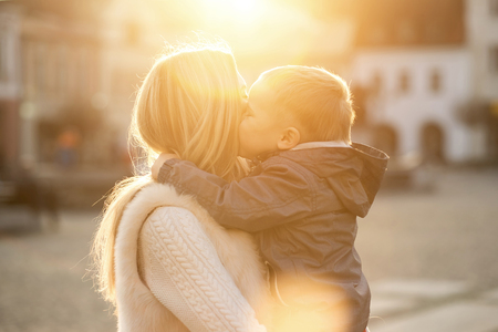 Foto de Happiness mother and son on the street at sunny day. - Imagen libre de derechos