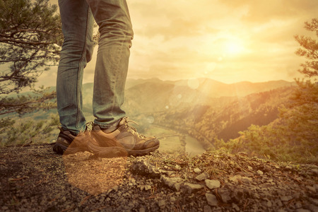 Foto de Men stay in Mountains footwear on the beautiful view. - Imagen libre de derechos