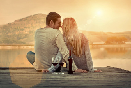 Foto de Romantic Couple sitting on the pier with red wine. - Imagen libre de derechos