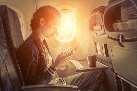 Foto de Woman sitting at airplane and looking to mobil phone. - Imagen libre de derechos