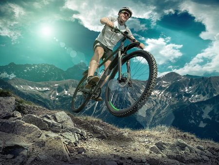 Photo for Man in helmet and glasses stay on the bicycle under sky with clouds. - Royalty Free Image