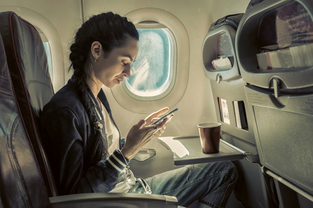 Photo pour Woman sitting at airplane and looking to mobil phone. - image libre de droit